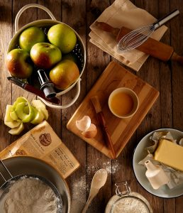 Ingredients and supplies for apple pie including apples, wisk, roller, flour, butter, spoon, bowl, egg, cream of tartar and cookbook on a wooden surface.