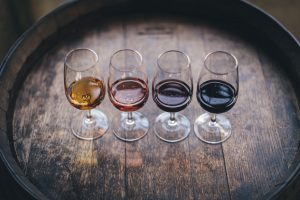 Four glasses of wine going from light to dark in color on brown oak barrel.