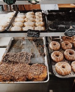 BAKERY ITEMS INCLUDING DOUGHNUTS IN A DELI CASE ON METAL TRAYS
