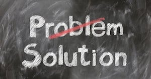 """BLACK CHALKBOARD WITH WORDS """"PROBLEM"""" AND """"SOLUTION"""" PROBLEM IS CROSSED OUT WITH RED LINE"""