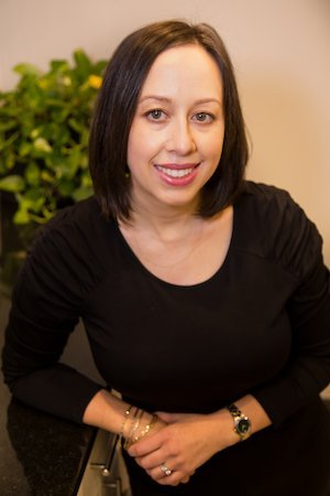 LISA HUGH REGISTERED DIETITIAN FOR SINGLE INGREDIENT GROCERIES LEANING ON BLACK COUNTER WITH GREEN PLANT IN BACKGROUND